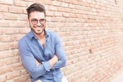Homme occasionnel se reposant près du mur de briques avec des mains croisées Image stock