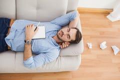 Homme occasionnel se trouvant sur le divan avec les papiers chiffonnés Photo libre de droits