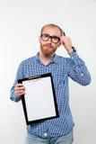 Homme occasionnel songeur montrant le presse-papiers vide images stock