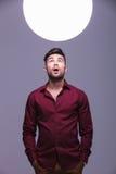 Homme occasionnel stupéfait regardant dans une sphère de lumière Image libre de droits
