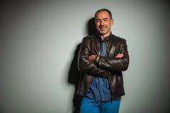 Homme occasionnel supérieur heureux dans la veste en cuir avec des mains croisées Photographie stock libre de droits