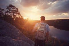 Homme occasionnel sur la falaise au-dessus de la rivière et regarder loin le coucher du soleil Photos stock