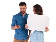 Homme occasionnel textotant près de la femme tenant la bulle vide de la parole Image stock