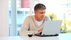 Homme occasionnel travaillant sur un ordinateur portatif clips vidéos