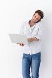 Homme occupé avec le sourire de mobile et d'ordinateur portable Photo stock