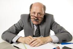 Homme occupé mûr supérieur d'affaires avec la tête chauve sur son fonctionnement 60s soumis à une contrainte et frustré au bureau image libre de droits