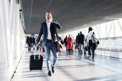 Homme occupé parlant du téléphone et marchant dans l'aéroport Photographie stock libre de droits