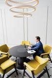 Homme occupé travaillant au carnet dans le bureau Photos libres de droits