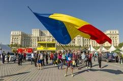 Homme ondulant le drapeau roumain géant Photographie stock