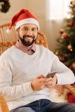 Homme optimiste dans le chapeau de Santa posant tout en textotant Photos libres de droits