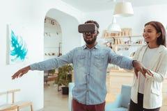 Homme optimiste essayant le nouveau casque de VR en café Image libre de droits
