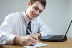 Homme ou étudiant d'affaires avec l'ordinateur portatif à la table Photo stock