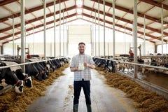 Homme ou agriculteur avec du lait de vaches à l'exploitation laitière Photos stock