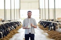 Homme ou agriculteur avec la cruche de lait de vaches à l'exploitation laitière Images stock