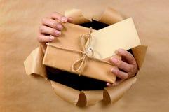 Homme ou facteur de messager livrant ou donnant le colis par le fond déchiré de papier brun photos stock