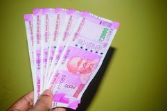 Homme ou femme d'affaires tenant ou payant ou donnant 2000 deux mille notes indiennes de roupies de devise de papier photo libre de droits