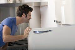 Homme ouvrant le réfrigérateur Photos stock