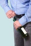 Homme ouvrant une bouteille de vin blanc image libre de droits