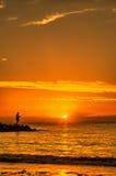 Homme pêchant outre du pilier au coucher du soleil Photographie stock