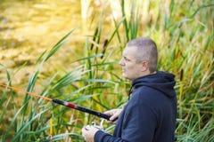 Homme pêchant près du lac Photographie stock libre de droits