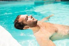 Homme paisible flottant dans la piscine Photos libres de droits