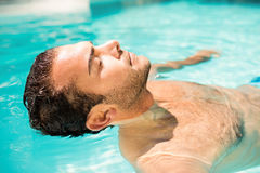 Homme paisible flottant dans la piscine Photo libre de droits