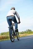 Homme par derrière le vélo d'équitation sur la route Image stock