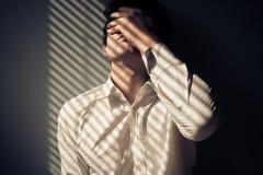 Homme par la fenêtre avec des ombres des abat-jour Image libre de droits