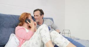 Homme parlant à la femme ayant l'appel téléphonique, couple heureux de famille se trouvant sur le lit dans la chambre à coucher banque de vidéos