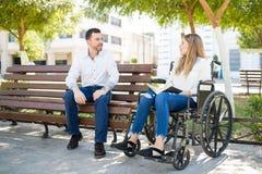 Homme parlant à la femme dans le fauteuil roulant Photos stock