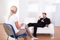 Homme parlant à son psychiatre Image stock