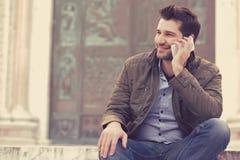 Homme parlant à un téléphone Professionnel occasionnel à l'aide du smartphone souriant à l'extérieur du vieux bâtiment image stock