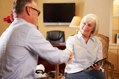 Homme parlant au conseiller féminin employant l'étiquette de Digital photos stock