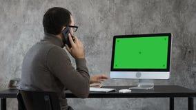 Homme parlant au téléphone dans le bureau et regardant sur l'écran d'ordinateur Affichage vert de maquette d'écran clips vidéos
