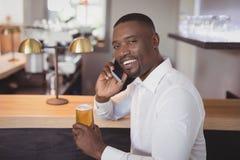 Homme parlant au téléphone portable tout en ayant la bière Photos libres de droits