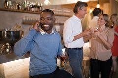 Homme parlant au téléphone portable tout en ayant la bière Images libres de droits