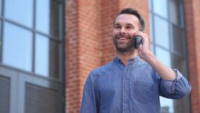 Homme parlant au téléphone tout en se tenant en dehors de l'immeuble de bureaux, discutant clips vidéos