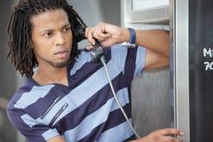Homme parlant sur la cabine téléphonique Photographie stock libre de droits