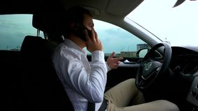 Homme parlant sur le smartphone dans la voiture banque de vidéos
