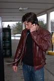 Homme parlant sur une cabine téléphonique Photos stock