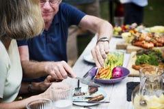 Homme partageant la nourriture à la femme à la partie de barbecue d'arrière-cour Image libre de droits