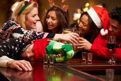 Homme passé sur la barre pendant les boissons de Noël avec des amis Photo stock