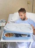 Homme patient dans la chambre d'hôpital après le plateau de souffrance de repas d'ouverture d'accidents prêt à prendre le déjeune Photographie stock libre de droits