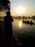 Homme payant le respect aux moines dans un bateau pendant le matin photo libre de droits