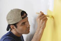 Homme peignant la couleur jaune sur le mur Images stock