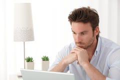 Homme pensant avec l'ordinateur portatif Image libre de droits