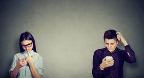 Homme perplexe et femme regardant le téléphone portable Images stock