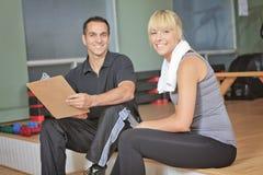 Homme personnel d'entraîneur de femme de gymnase avec le matériel de formation de poids Image stock