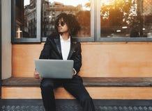 Homme philippin sur le banc de rue avec le netbook près du café photos libres de droits