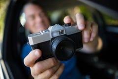 Homme photographiant avec l'appareil-photo dans la voiture Images stock